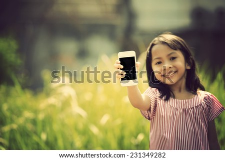 Happy asian girl playing with cellphone at outdoor in sunny day with retro style - stock photo
