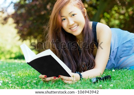 Happy asian girl reading a book at the park