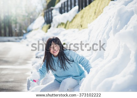 Happy asian girl smiling outdoors in snow on cold winter day - stock photo