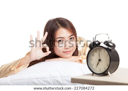 Happy Asian girl  wake up show OK with alarm clock  isolated on white background - stock photo