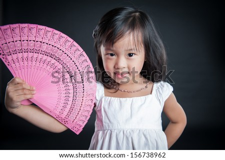 happy asian girl with a pink fan. isolated on black background - stock photo
