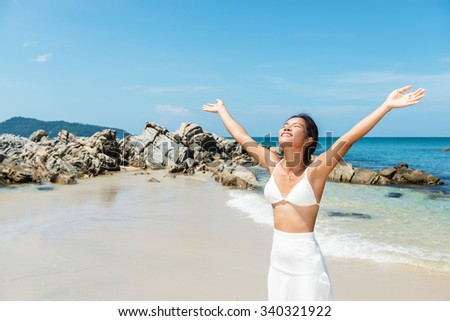 Happy Asian girl with arms outstretched enjoys on the tropical Thai beach.Copy space - stock photo