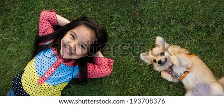 Happy Asian girl with her doggy portrait lying on lawn - stock photo