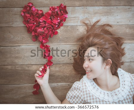 Happy asian girl with red rose heart shape on old wood background, use filter images - stock photo