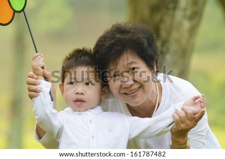 happy asian grandmother with grandson child playing outdoor - stock photo