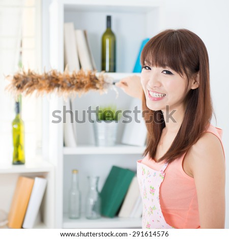 Happy Asian housewife with apron cleaning house, hand holding a duster and smiling. Young woman indoors living lifestyle at home.