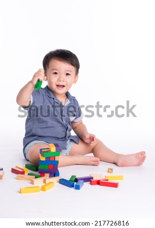 happy asian kid playing with educational blocks toy