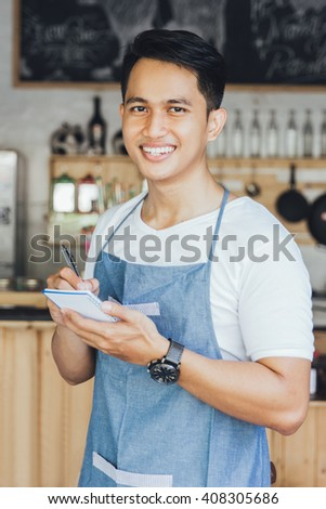 Happy asian male waiter in apron writing order and looking at camera - stock photo