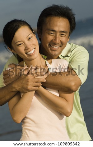 Happy asian man embracing woman from behind on the beach