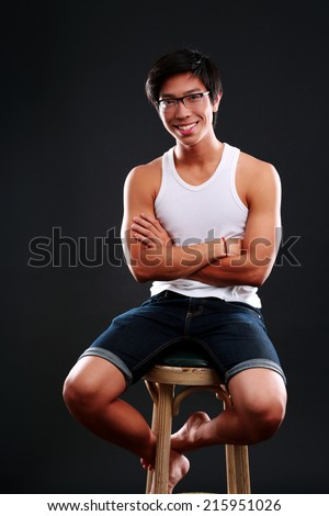 Happy asian man in glasses sitting on the chair over black background - stock photo
