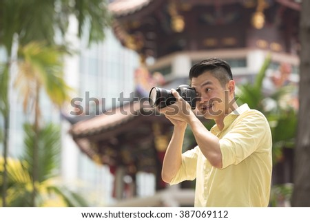 Happy Asian man on holiday using his digital camera (DSLR) to take a photo. Chinese temple in the background.