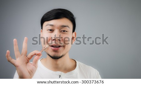 Happy Asian man with chicken bone. - stock photo