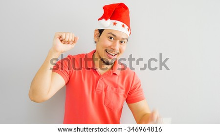 Happy asian man with Santa Claus hat. - stock photo