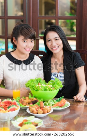 Happy Asian mother and daughter having lunch together - stock photo