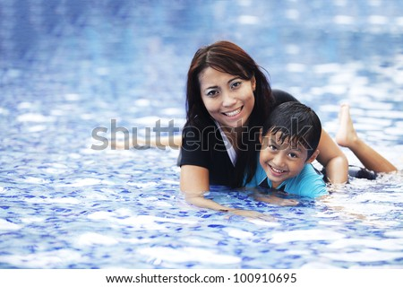 Happy Asian mother and son posing at swimming pool