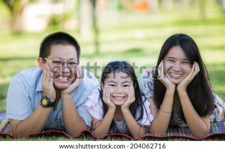 Happy asian mother, father and daughter relax in the park - stock photo