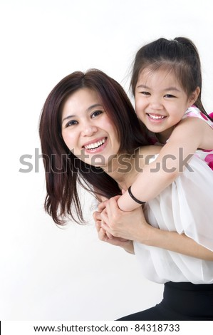 happy asian mother giving her daughter a piggyback ride - stock photo