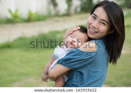 Happy asian mother with adorable cute baby - stock photo