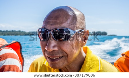 Happy Asian old man going out to the sea.