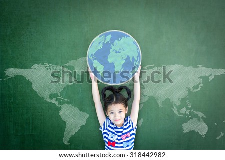 Happy Asian school girl kid child raising hands holding globe on green chalkboard with global world map background & empty copy space for adding texts: Child's education for world literacy day concept - stock photo