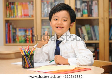 Happy Asian schoolboy wearing white shirt and tie sitting at desk gesturing thumbs up - stock photo