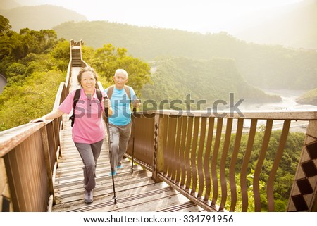 happy  asian senior couple hiking on the mountain  - stock photo
