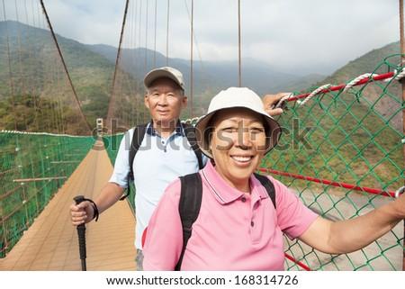 happy asian senior couple walking on the bridge in the nature park - stock photo