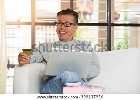 happy asian senior shopping online with credit card