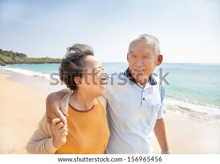 happy asian seniors walking on the beach - stock photo