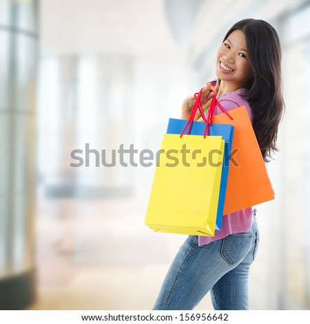 Happy Asian shopping woman smiling holding many shopping bags at the mall. Casual Asian shopper girl standing in department store. Beautiful mixed race Southeast Asian woman model. - stock photo