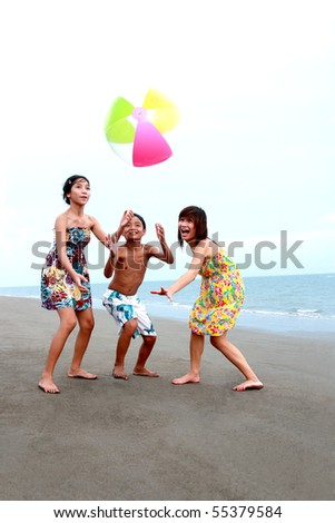 happy asian teenagers playing at the beach