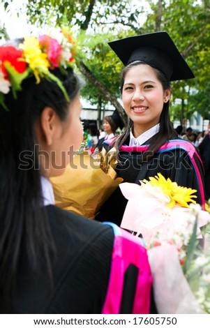 Happy Asian university graduates celebrates their success. - stock photo
