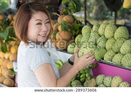 Happy asian woman choosing fresh custard apple fruit in the grocery shop on the foreground - stock photo