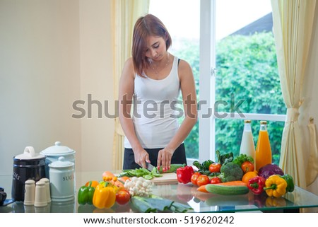 Happy asian woman cooking vegetables green salad in the kitchen