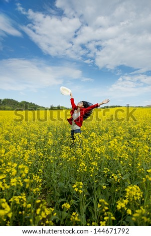 happy asian woman in a canola field - stock photo