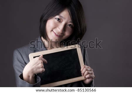 Happy Asian woman in suit pointing to blank blackboard - stock photo