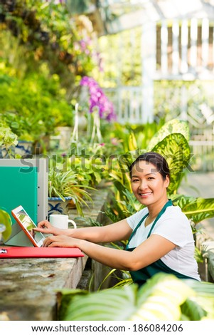 Happy Asian woman taking care of green plants in the garden - stock photo