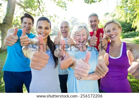 Happy athletic group with thumbs up on a sunny day - stock photo