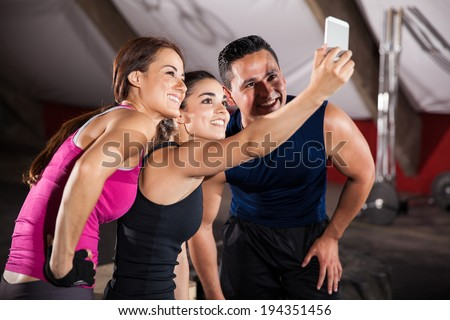 Happy athletic guys taking a group selfie after finishing their workout in a cross-training gym - stock photo