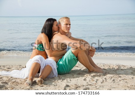 Happy attractive affectionate young couple sunbathing together on the beach in their swimwear while enjoying a tropical summer holiday during the annual vacation