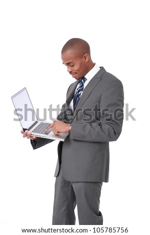 Happy attractive African American businessman standing wearing corporate grey suit and blue tie holding a laptop computer in one hand looking down while typing on keyboard isolated on white background
