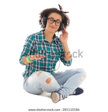 happy attractive african american teenage girl sitting and listening music isolated on white background - stock photo