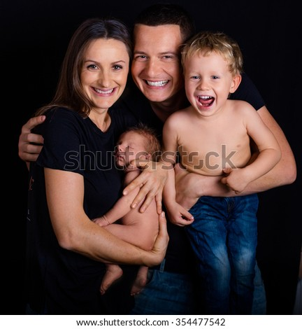 Happy Attractive Beautiful family with their son and newborn baby boy - stock photo