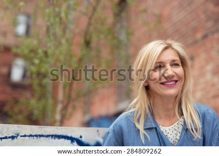 Happy attractive blond woman in town smiling with pleasure as she looks into the air in front of a blurred brick building with copyspace - stock photo