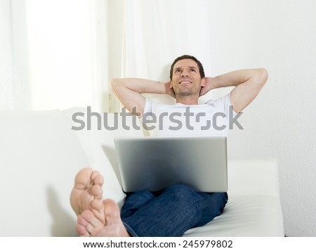happy attractive Brazilian man freelance working with computer laptop laying on couch at home relaxed thinking and dreaming of future successful work project - stock photo