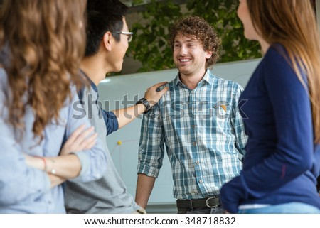Happy attractive confident young curly man in plaid shirt getting support of his colleagues in the office - stock photo