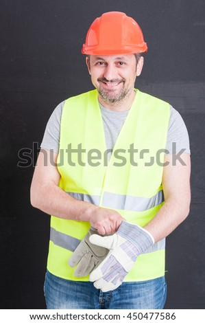 Happy attractive constructor getting ready for work and putting gloves on isolated on black background