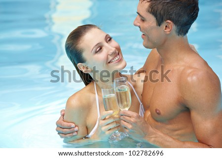Happy attractive couple drinking sparkling wine in swimming pool - stock photo