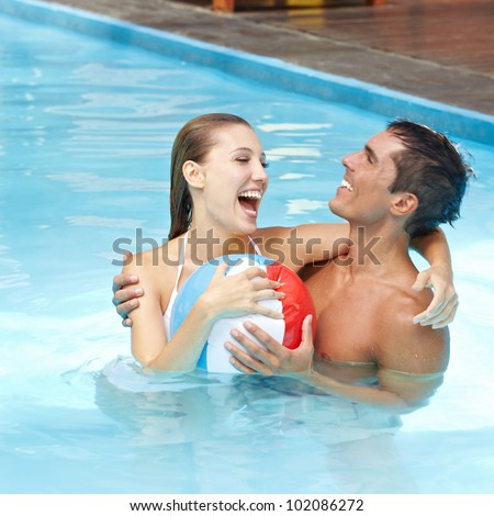 Happy attractive couple having fun in pool with beach ball - stock photo