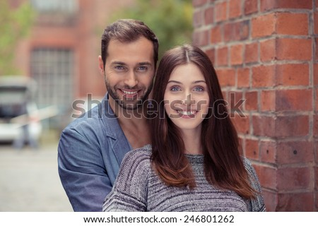 Happy attractive couple in an urban street standing in a close embrace facing the camera with warm friendly smiles against a brick wall - stock photo